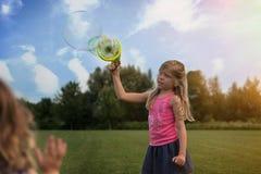 A menina caucasiano loura bonito está fazendo bolhas no campo imagens de stock