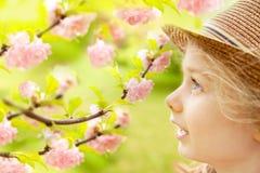 A menina caucasiano loura da criança admira o jardim de florescência Fotografia de Stock Royalty Free