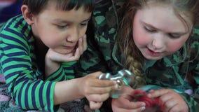 Menina caucasiano loura e um menino multi-étnico que joga em casa com um brinquedo 4K do girador filme