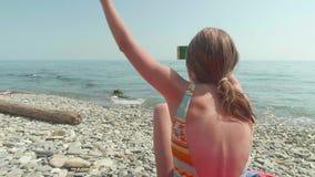 A menina caucasiano loura nova com um smartphone está jogando os braços acima contra o mar, movimento lento video estoque