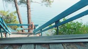 A menina caucasiano loura nova da hippie na doca de madeira si mesmachama- contra o mar vídeos de arquivo