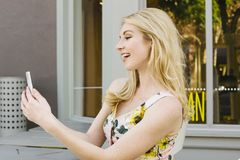 A menina caucasiano loura sorri em um telefone celular e está feliz fotografia de stock royalty free