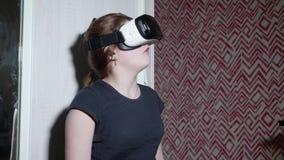Menina caucasiano nas tentativas dos vidros de VR para olhar suas mãos vídeos de arquivo