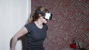 A menina caucasiano nos vidros de VR que vestem para trás o tshirt é assustado e preocupada A menina está receosa da realidade vi filme