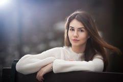 Menina caucasiano nova atrativa que veste uma blusa branca que senta-se em um banco no parque Menina adolescente do cabelo marrom Fotografia de Stock