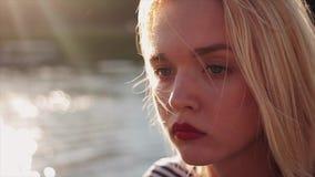 Menina caucasiano nova bonita com cabelo louro e os bordos vermelhos no por do sol na frente da água Retrato, fim acima do tiro filme