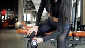 Menina caucasiano nova da forma atrativa que faz exercícios do bíceps ao sentar-se no banco e ao levantar o peso no gym vídeos de arquivo