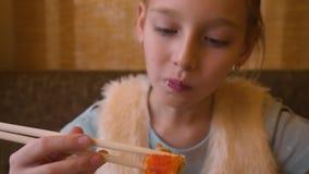 Menina caucasiano nova que come o alimento do sushi no restaurante japonês com varas vídeos de arquivo