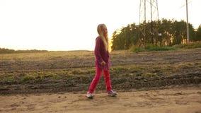 Menina caucasiano nova que dança e que canta fora Staing no por do sol rural do outono da cena do campo Handheld vídeos de arquivo