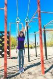 Menina caucasiano nova que faz esportes nos anéis na plataforma da rua Fotografia de Stock