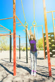 Menina caucasiano nova que faz esportes nos anéis na plataforma da rua Imagens de Stock