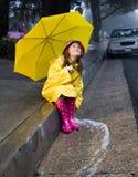 Menina caucasiano nova que joga na chuva Fotos de Stock Royalty Free