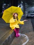 Menina caucasiano nova que joga na chuva Imagens de Stock Royalty Free