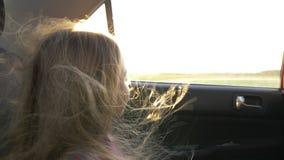 Menina caucasiano nova que olha ao horizonte à janela de carro Abra a janela e o forte vento de carros que vibram seus cabelos Fi vídeos de arquivo