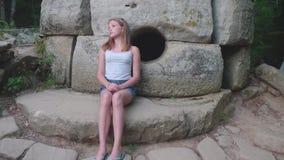 A menina caucasiano nova senta-se pensativamente em um dólmem antigo filme