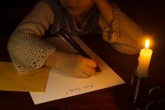 Menina caucasiano pequena que escreve uma letra a Santa Imagem de Stock