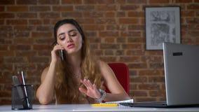 A menina caucasiano preocupada bonita está tendo a conversa telefônica que senta-se em seu desktop com o tijolo vermelho no fundo vídeos de arquivo