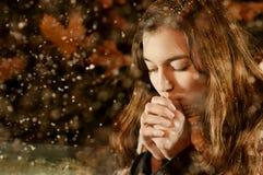 Menina caucasiano que aquece-se na queda de neve Fotografia de Stock