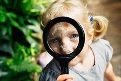 A menina caucasiano que olha plantas floresce o antúrio através da lupa Fotos de Stock Royalty Free