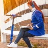A menina caucasiano ruivo em um revestimento azul olha no portátil ao sentar-se em um banco de parque no por do sol Uma jovem mul imagens de stock