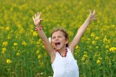 Menina cercada por flores do rapeseed Fotografia de Stock Royalty Free