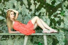 menina charming que encontra-se em um banco de madeira Fotos de Stock