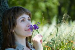 A menina cheira flores Fotografia de Stock Royalty Free