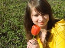 A menina cheira uma flor imagens de stock royalty free