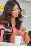 Menina chinesa asiática da mulher na cozinha usando o tablet pc fotos de stock