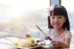 Menina chinesa asiática de sorriso que come o bife do cordeiro com arroz imagem de stock
