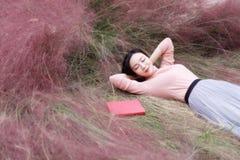 A menina chinesa asiática feliz da mulher que encontra-se no sonho da grama reza o conhecimento lido natureza do livro da esperan fotografia de stock