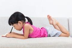 Menina chinesa asiática que coloca no livro da escrita do sofá Imagens de Stock