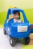 Menina chinesa asiática que conduz o carro do brinquedo imagem de stock royalty free