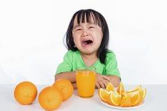 Menina chinesa asiática que grita para o suco de laranja Imagem de Stock Royalty Free