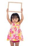 Menina chinesa asiática que guarda o whiteboard vazio Imagens de Stock Royalty Free