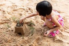 Menina chinesa asiática que joga a areia na praia imagem de stock