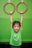 Menina chinesa asiática que pendura em anéis Imagem de Stock Royalty Free