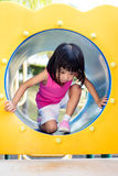 Menina chinesa asiática que rasteja no campo de jogos Fotografia de Stock