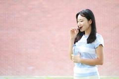 A menina chinesa asiática relaxado aprecia o tempo livre, come o petisco Fotografia de Stock Royalty Free