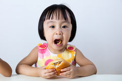 Menina chinesa asiática que come o hamburguer Imagens de Stock Royalty Free