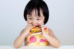 Menina chinesa asiática que come o hamburguer Fotografia de Stock