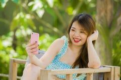 Menina chinesa coreana feliz e atrativa nova no jardim do recurso que toma a foto do selfie com câmera do telefone celular que ap fotos de stock royalty free