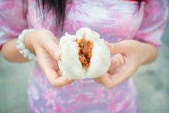 A menina chinesa no cheongsam está rasgando o bolo cozinhado do material cozinhado Fotografia de Stock