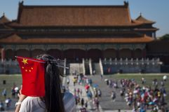 Menina chinesa nova com uma bandeira chinesa em sua cabeça na Cidade Proibida na cidade do Pequim, em China Fotos de Stock