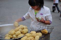 Menina chinesa nova que vende batatas na rua imagens de stock