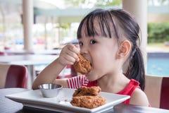 Menina chinesa pequena asiática que come o frango frito Imagens de Stock Royalty Free