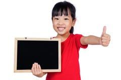 Menina chinesa pequena asiática que guarda um quadro-negro com polegares-acima imagens de stock