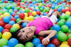 Menina chinesa pequena asiática que joga com as bolas plásticas coloridas imagem de stock royalty free