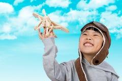 Menina chinesa pequena asiática que joga com Toy Airplane Fotografia de Stock Royalty Free