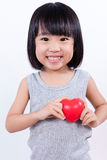 Menina chinesa pequena asiática que guarda o coração vermelho Imagem de Stock Royalty Free